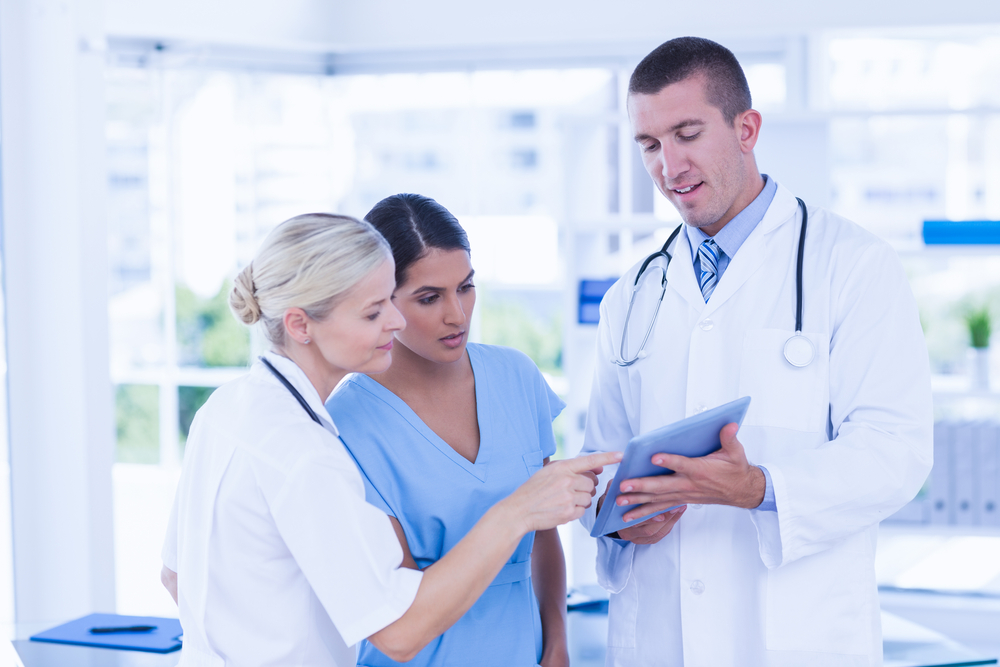 Doctors looking together at tablet in medical office
